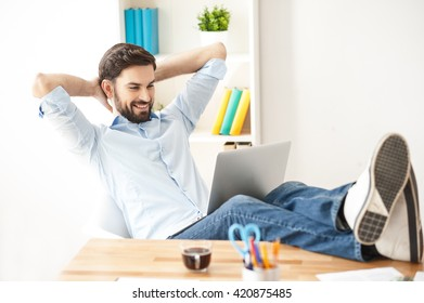 Attractive guy is relaxing with a notebook