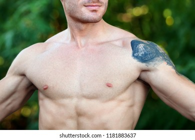 Attractive guy showing his muscles and a big tattoo on the shoulder