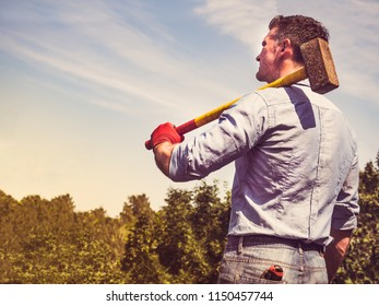 Attractive guy with a sledgehammer on his shoulders, looking into the distance against the background of green trees, blue sky and sunset. View from the back. Labour Day concept