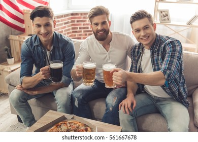 Attractive guys are clinking glasses of beer, looking at camera and smiling while resting at home