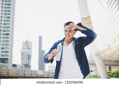 Attractive handsome asian man gets thirsty because of hot weather in the summer season. Cool guy feels exhausting and holds the bottle of cold water. He wears denim jacket. copy space, city background