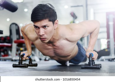 Attractive Handsome Asian young men workout with push up bar in gym focus on muscle feeling so strong and powerful,Bodybuilder concept