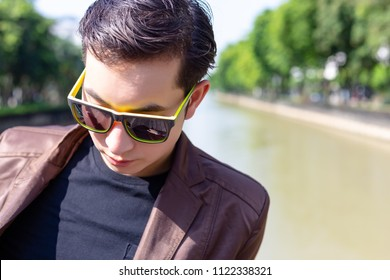 Attractive handsome businessman get depressed, stressed because handsome business man gets jobless or unemployment. Handsome cool guy stand at outdoor and thinking about his life. He wear sunglasses