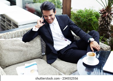 Attractive and handsome businessman using mobile phone, asian businessman having a phone talk, wealthy man talking on the smart phone seated in the terrace of modern lounge cafe at his work break