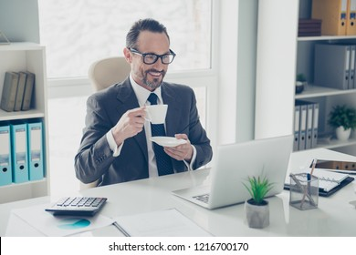 Attractive handsome dreamy man in trendy style stylish tux formal wear look on modern technology screen monitor sit on armchair behind desktop in bright lite workplace office hold beverage in hands