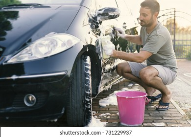 Attractive handsome man washing car with sponge and foam