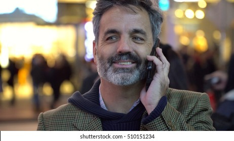 Attractive handsome older man, grey hair beard, talking on smart mobile cell phone on street in New York City. Successful hipster urban businessman.
