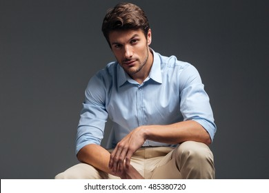 Attractive handsome serious man sitting and looking at camera over grey background