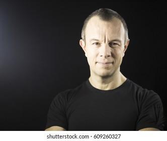 Attractive  handsome slim healthy man aged in 40's in black t-shirt against plain black studio portrait background.