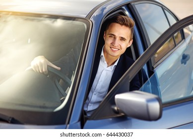 Attractive handsome smiling man in a business suit driving an expensive car