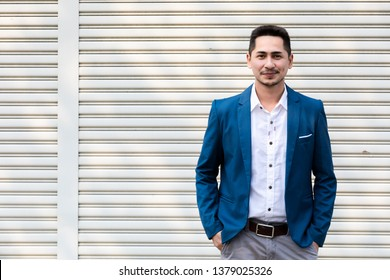 Attractive handsome smiling positive asian happy business man. Closeup portrait asian young man wearing suit on metal sheet background copy space.