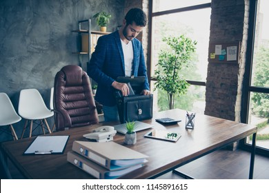 Attractive handsome young brunet bearded executive worker serious man, accountant at work station work place. Finishing, collecting things after work day goes home