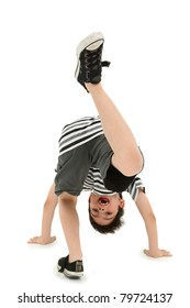 Attractive happy boy doing cartwheel on white floor.
