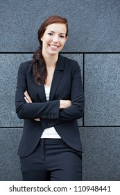 Attractive happy businesswoman leaning on a wall with arms crossed