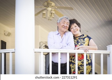 Attractive Happy Chinese Couple Enjoying Their House Outside.