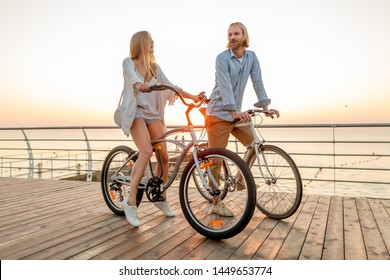 attractive happy couple of friends traveling in summer on bicycles, man and woman with blond hair boho hipster style fashion having fun together, walking by the sea in resort city