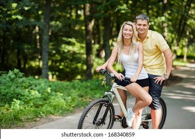 Attractive happy couple on a bicycles in a countryside