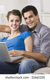 An attractive and happy couple sitting together on a couch and using a laptop.  They are smiling directly at the camera.  Vertically framed shot.