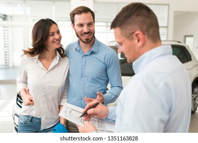 Attractive happy excited young couple buying a new car, seller is signing papers for a car leasing in car salon. Buying new car with bank loan concept.