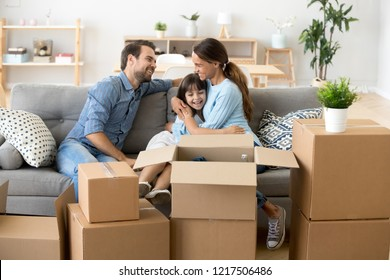 Attractive happy family with little adorable child sitting on couch in living room at new home. Loving mother embrace small daughter talking have fun together indoors. Buying property and loan concept