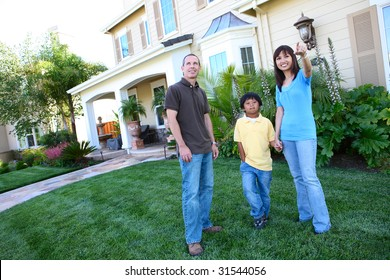 Attractive happy family outside their home having fun