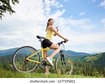 Attractive happy female cyclist riding on yellow mountain bike on a grassy hill, showing thumbs up, enjoying summer day in the mountains. Outdoor sport activity, lifestyle concept