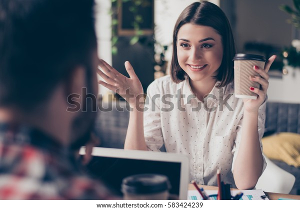 Attractive happy female manager with coffee talking with colleague