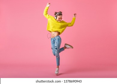 attractive happy funny woman jumping listening to music in headphones dressed in hipster colorful style outfit isolated on pink studio background, wearing yellow sweater and sunglasses, having fun