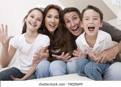 An attractive happy, laughing family of mother, father, son and daughter sitting on a sofa at home having fun