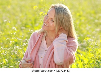 Attractive happy mature woman enjoys life on a walk in a flowerfield
