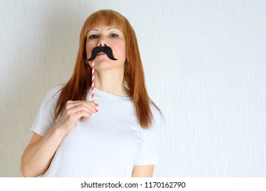 Attractive happy middle aged woman having fun with a fake moustache on stick. Senior  female in period menopause. Lifestyle, Women's Health concept : playful  mature ready for party. Impostor syndrome