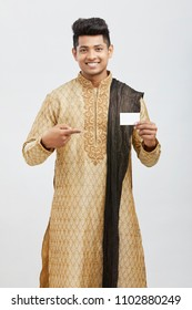 Attractive happy north Indian young man holding business card on white.