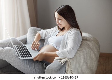 Attractive happy pregnant woman watching videos about maternity and giving birth with laptop, lying in armchair holding notebook on laps, smiling with cute and intrigued expression at screen of device