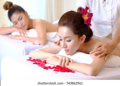 Attractive Happy relaxing asian girl at beauty spa treatment. Beauty young woman recieving  massage at spa, massager's hands on the woman's body spa concept. Young woman with Glow, and pefect Skin.