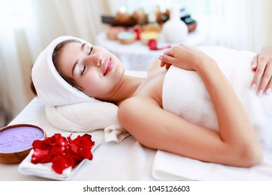 Attractive Happy relaxing girl at beauty spa treatment. Beauty young woman lying down on massage beds at Asian luxury spa and wellness center. Spa, beauty concept.