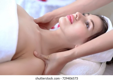 Attractive Happy relaxing girl at beauty spa treatment. Beauty young woman recieving Shoulder massage at spa. , massager's hands on the woman's shoulder spa concept.