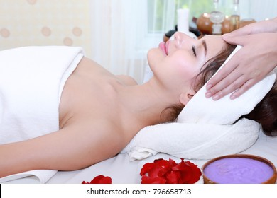 Attractive Happy relaxing girl at beauty spa treatment. Beauty young woman recieving head massage at spa, massager's hands on the woman's head spa concept. Young woman with Glow, and pefect Skin.
