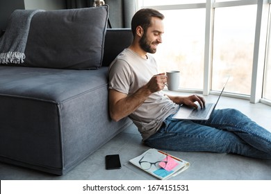 Attractive happy smart young man sitting on a floor in the living room, working on ;laptop computer, drinking coffee
