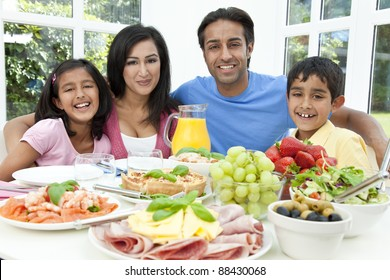 An attractive happy, smiling Asian Indian family of mother, father, son and daughter eating healthy food & salad at a dining table.