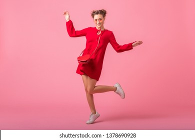 attractive happy smiling stylish woman in red trendy dress jumping running on pink studio background isolated, spring summer fashion trend, romantic mood flirty girl