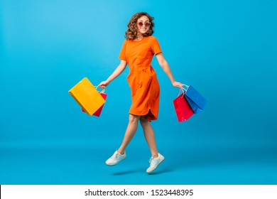 attractive happy smiling stylish woman shopaholic in orange trendy oversize dress jumping running holding shopping bags on blue studio background isolated, colorful, sale excited, fashion trend