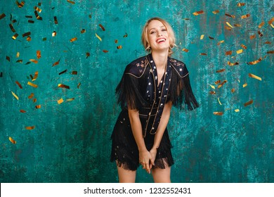 attractive happy smiling woman in stylish black dress with fringe dancing, celebrating Christmas and new year, golden confetti flying, party style, having fun, green blue vintage wall background