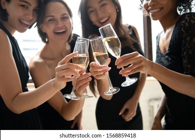 Attractive happy stylish young ladies hold clinking glasses with toast looking at camera, smiling multiethnic girls wear black elegant dresses drink champagne celebrate party concept, close up view
