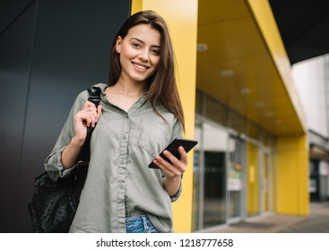 Attractive happy woman with beautiful smile using mobile phone and application for online shopping with discount sales. Positive hipster blogger blog post, streaming video, walking on the street.