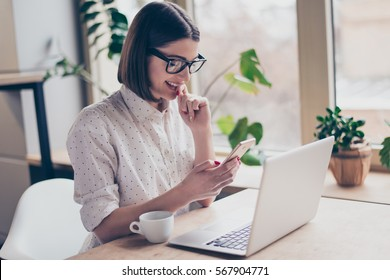 Attractive happy woman with laptop reading sms in office.