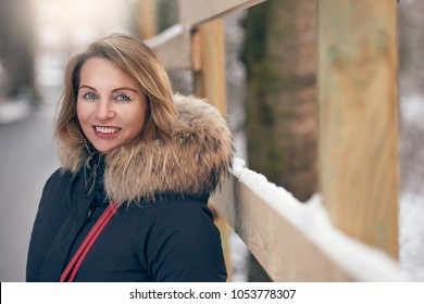 Attractive happy woman standing outdoors in winter wearing a fur trimmed jacket alongside a widow sill with fresh white snow in an urban street looking to the side with a smile and copy space