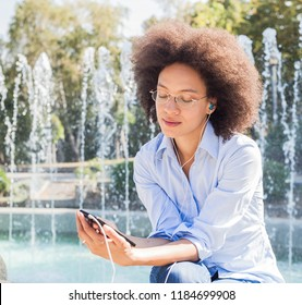 Attractive Happy Young African American Woman In Casual Wear, Sitting Near Fountain, Listening Music By Earphones