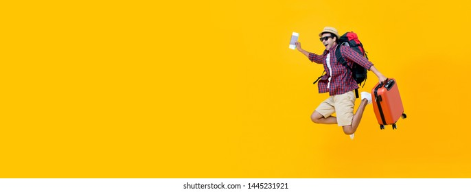 Attractive happy young Asian man tourist with air ticket and passport  jumping isolated on yellow banner  background with copy space