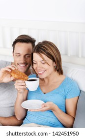 Attractive happy young couple sitting up against the pillows enjoying a delicious coffee and croissant in bed
