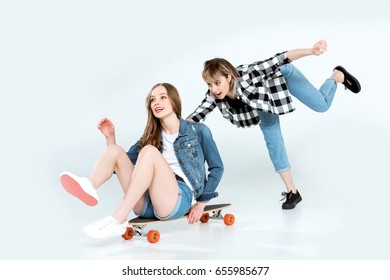 Attractive happy young girlfriends having fun with skateboard isolated on grey